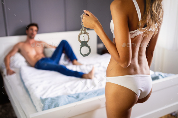 Woman and man playing domination games in bed - Stock Photo - Images