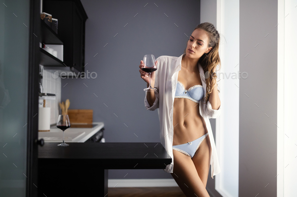 Sexy brunette female in white male shirt over lingerie holding red wine in a glass - Stock Photo - Images