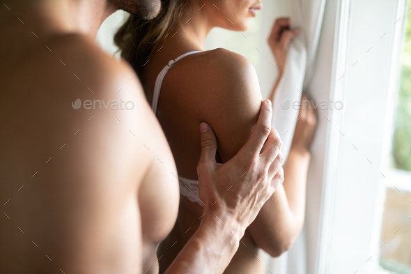 Attractive couple sharing intimate moments in bedroom - Stock Photo - Images