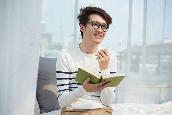 Young man enjoying a book - Stock Photo - Images
