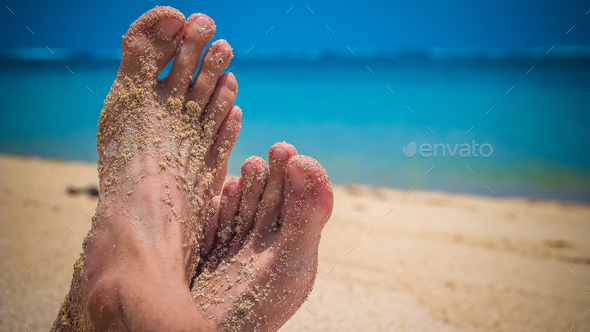 Male Cross Feet at the Sandy Beach, Ocean in Background, Bali - Stock Photo - Images