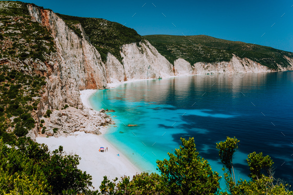 Amazing Fteri beach lagoon, Kefalonia, Greece. Tourists under umbrella chill relax near clear blue - Stock Photo - Images