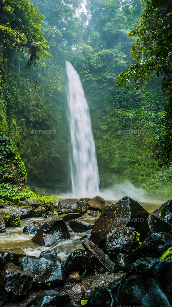Amazing Nungnung waterfall, Huge Rocks in front, Bali, Indonesia - Stock Photo - Images