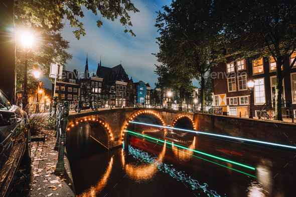 Light trails at famous canals in Amsterdam at dusk. Long exposure shot - Stock Photo - Images