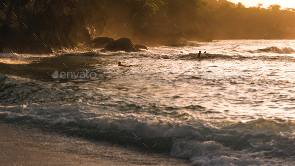 Local Kids surf on Waves in Sunset light, Beautiful Crystal Bay, Nusa Penida Bali - Stock Photo - Images