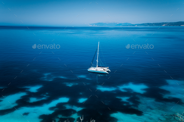 Fteri beach Kefalonia, Greece. White catamaran yacht in clear blue transparent sea with dark pattern - Stock Photo - Images