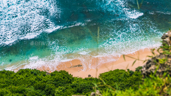 Aerial view of pure clear turquoise colored waves rolling on tropical sandy beach on sunny day - Stock Photo - Images