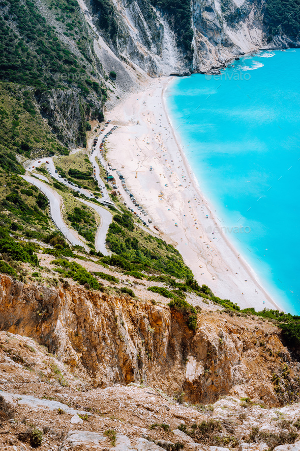 Serpentine zigzag road down to famous Myrtos Beach. Many tourists on the sunny beach, Kefalonia - Stock Photo - Images