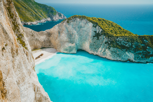 Famous shipwreck on Navagio beach with turquoise blue sea water surrounded by huge white cliffs - Stock Photo - Images