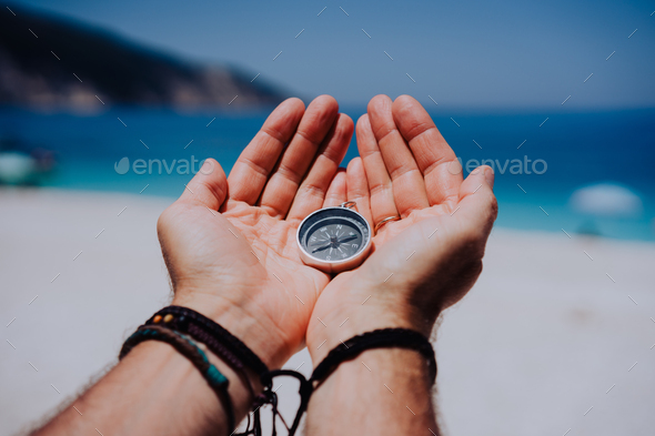 Open hand palms with metal compass on the sandy beach. Searching your way concept. Blue sea in - Stock Photo - Images