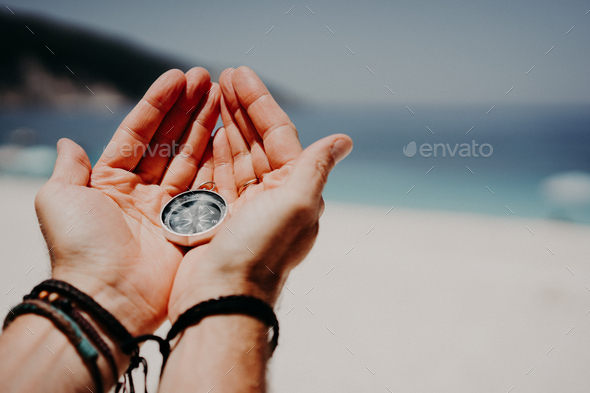 Man's hand holding compass against the backdrop of beach and sea. The concept of travel, summer - Stock Photo - Images