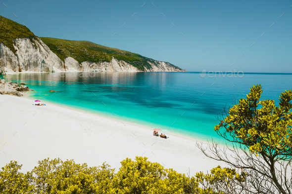 Amazing Fteri beach lagoon, Cephalonia Kefalonia, Greece. Tourists under umbrella relax near clear - Stock Photo - Images