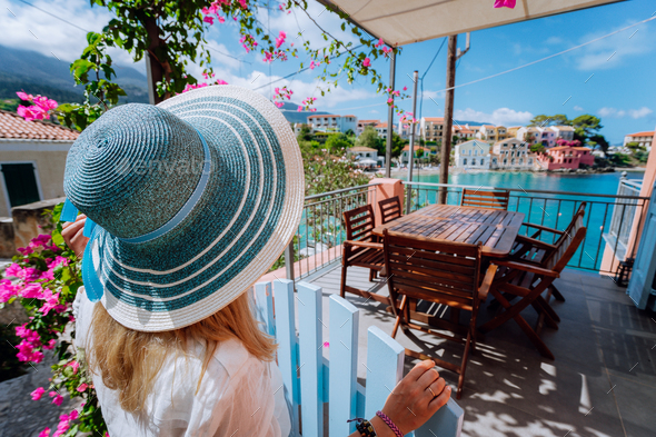 Assos village, Kefalonia, Greece. Female tourist in blue sunhat in front of cozy veranda terrace - Stock Photo - Images