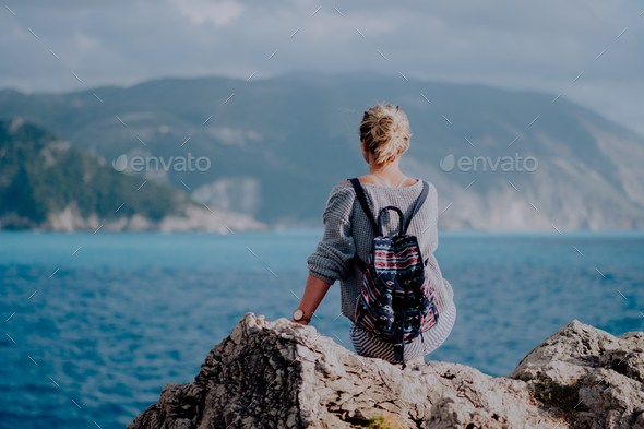 Woman with colorful backpack siting on rocky shore looking to the sea and island on the horizon - Stock Photo - Images