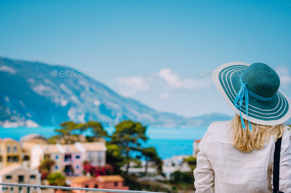 Tourist woman wear blue sunhat and white clothes admire view of colorful tranquil village Assos on - Stock Photo - Images