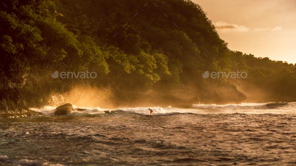 Local Kids surf on Waves in Sunset light, Beautiful Crystal Bay, Nusa Penida Bali - Stock Photo - Images