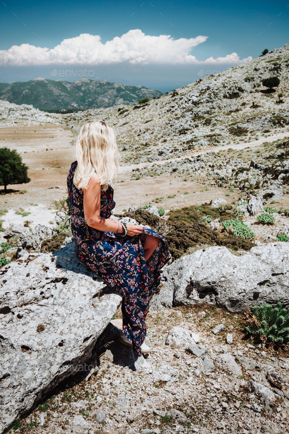 Tanned girl in beautiful dress sitting alone on the stone in the mountainous scenery of highland - Stock Photo - Images