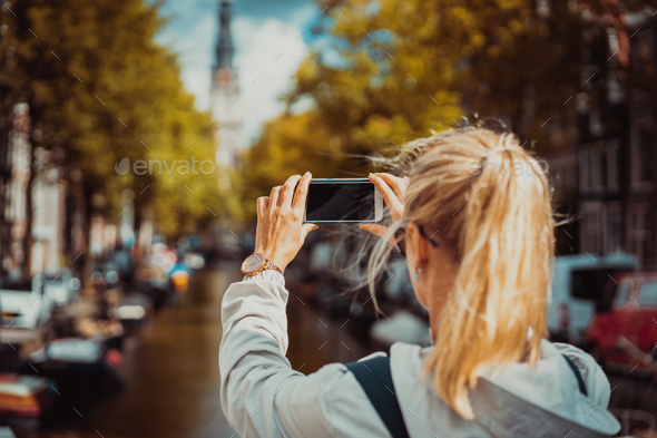 Woman tourist taking a picture of canal in Amsterdam on the mobile phone. Warm gold afternoon - Stock Photo - Images