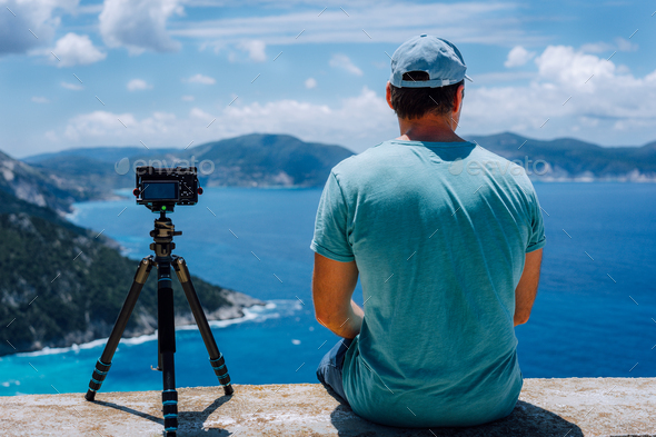 Travel Europe summer holiday in Greece. Happy man photographer enjoying cloudscape, coastline and - Stock Photo - Images