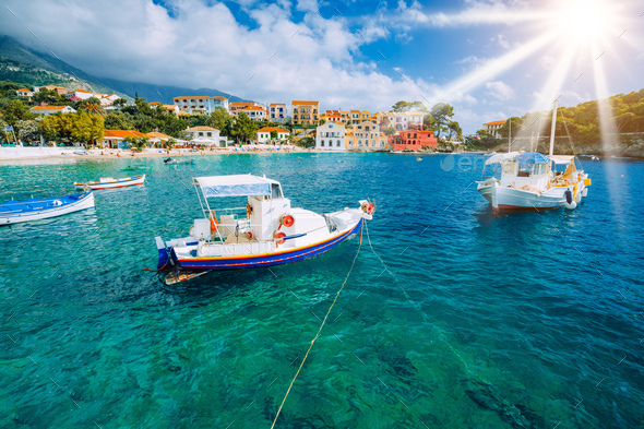 Cozy Assos village in Kefalonia. Colorful boats in azure bay under morning sunlight. Sommer vacation - Stock Photo - Images