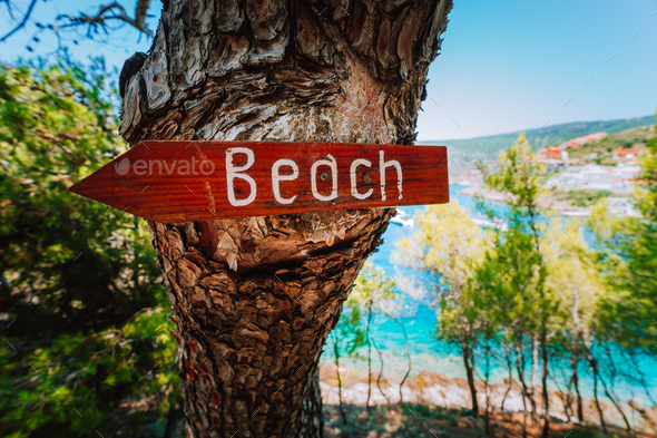 Assos village in morning light, Kefalonia. Greece. Beach wooden arrow sign on a pine tree showing - Stock Photo - Images
