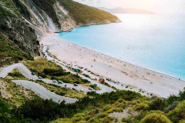 View of serpentine road lead to Famous Myrtos Beach, Kefalonia, Greece. Visiting amazing blue bay - Stock Photo - Images