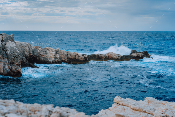 Sea waves splashing against rocky coastline. Dramatic cloudscape before sunderstorm - Stock Photo - Images