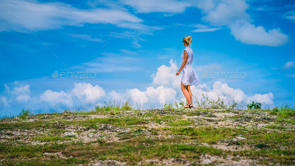 A girl standing on Hill and looking at the white clouds, Teletubbies Hills, Nusa Penida, Bali - Stock Photo - Images