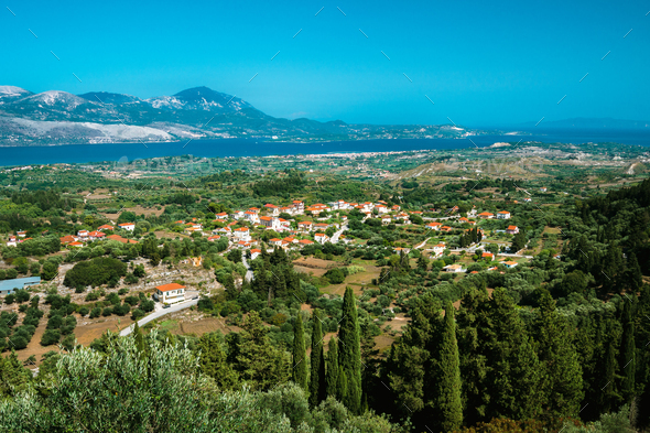 View of idyllic valley town with red roofs on mediterranean island. Olive groves, cypresses and blue - Stock Photo - Images