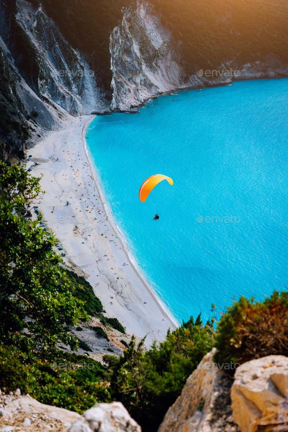 Myrtos Beach, Kefalonia Island, Greece. Figure of a parachutist skydiver with orange parachute - Stock Photo - Images