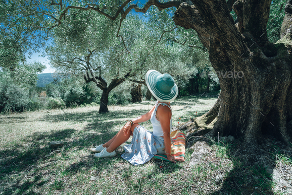 Young woman with straw sun hat under an olive tree on a background of idyllic Mediterranean - Stock Photo - Images