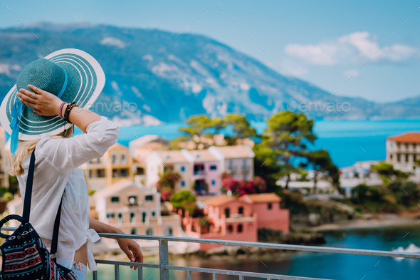 Tourist woman wearing blue sunhat and white clothes enjoying view of colorful tranquil village Assos - Stock Photo - Images