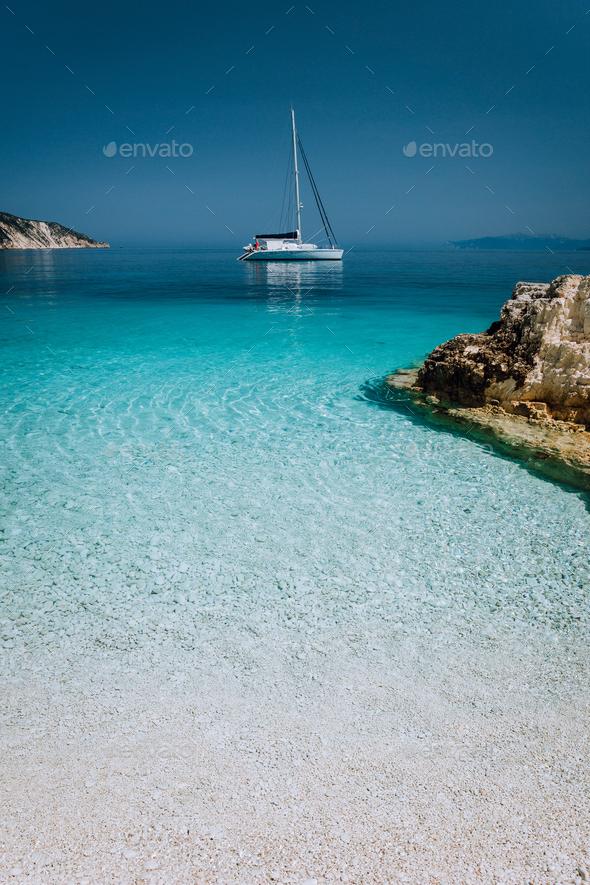 Beautiful azure blue lagoon with sailing catamaran yacht boat at anchor. Pure white pebble beach - Stock Photo - Images