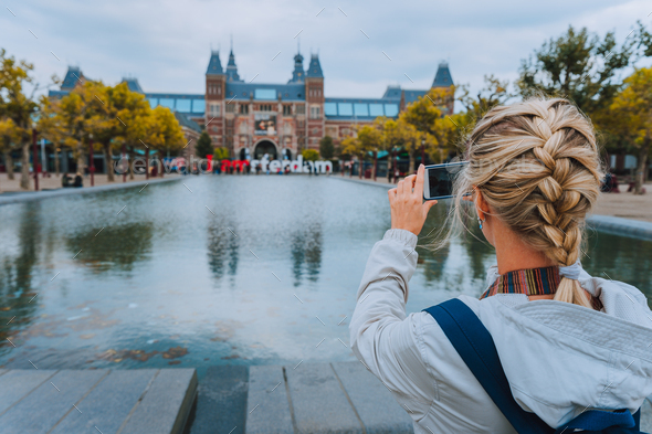 Woman tourist taking photo of the Rijksmuseum in Amsterdam on the mobile phone. Travel in Europe - Stock Photo - Images