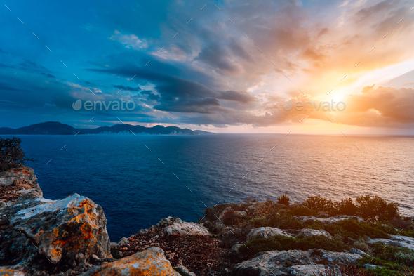 Dramatic sunset on the coastline. Motion clouds on horizon, rainy weather - Stock Photo - Images