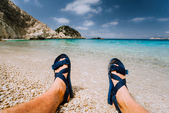 Young male feets wear blue flip-flop sandal sunbathing on sea beach with clear water - Stock Photo - Images