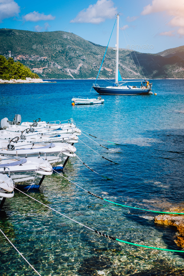 Small tourist boats for rent docked on the shore. Turquoise bay, crystal clear water. Amazing summer - Stock Photo - Images