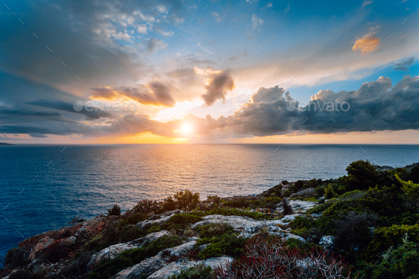 Dramatic moody sunset on the coastline near Assos place on Kefalonia Island. Motion clouds on - Stock Photo - Images