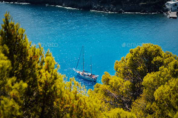 White yacht take a shelter in beautiful blue lagoon of Assos village Kefalonia. Frame between top of - Stock Photo - Images