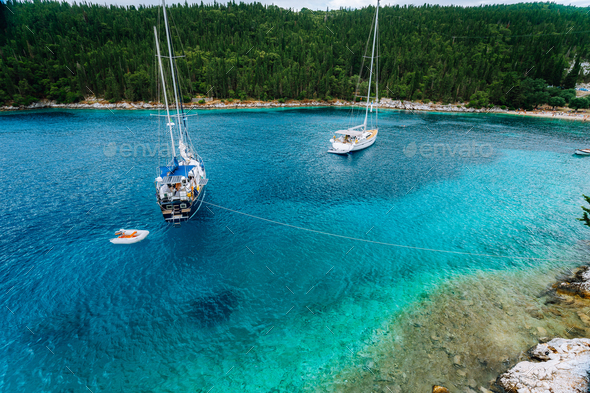 Crystal clear transparent blue turquoise teal mediterranean sea water of Foki Fiskardo Beach with - Stock Photo - Images