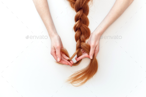 Woman with red hair braids a pigtail isolated on white background. - Stock Photo - Images