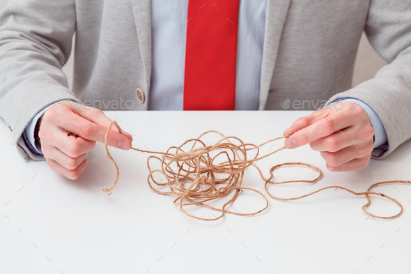 Alone businessman try to unwinds tangled thread ball like puzzle out situation. Conceptual photo. - Stock Photo - Images