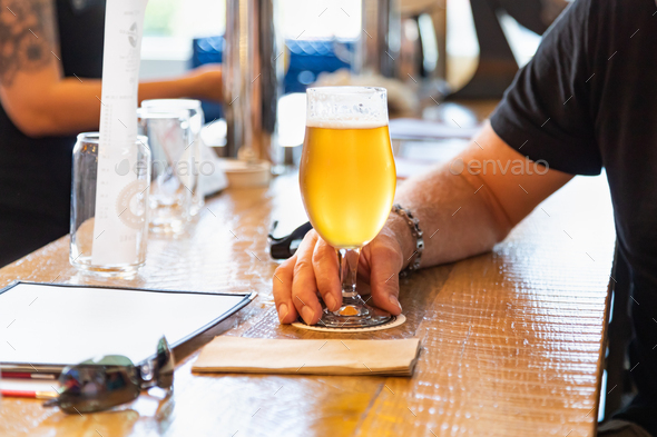 Man Holding Glass of Micro Brew Beer at Bar - Stock Photo - Images