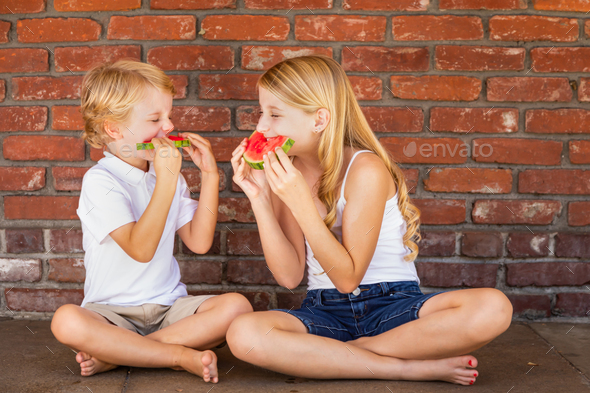 Cute Young Cuacasian Boy and Girl Eating Watermelon Against Brick Wall - Stock Photo - Images