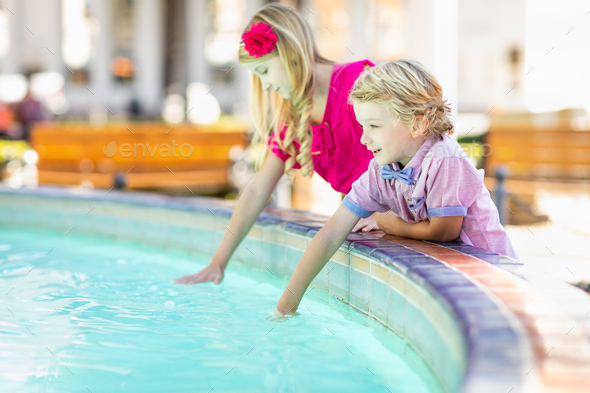 Cute Young Caucasian Brother and Sister Enjoying The Fountain At The Park - Stock Photo - Images
