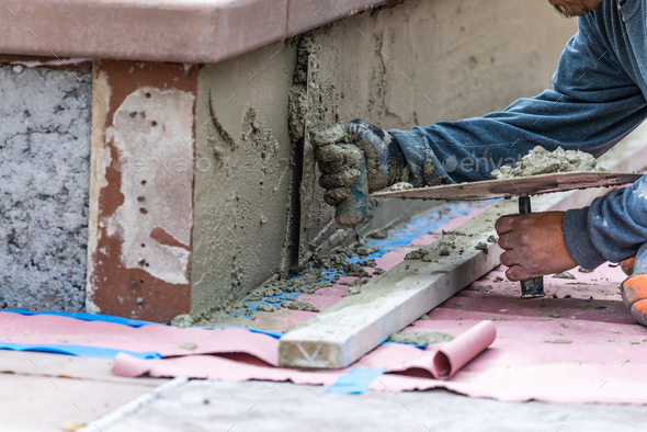Tile Worker Applying Cement with Trowel at Pool Construction Site - Stock Photo - Images
