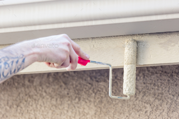 Professional Painter Using Small Roller to Paint House Fascia - Stock Photo - Images