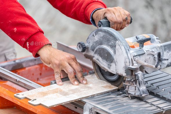 Worker Using Wet Tile Saw to Cut Wall Tile At Construction Site - Stock Photo - Images