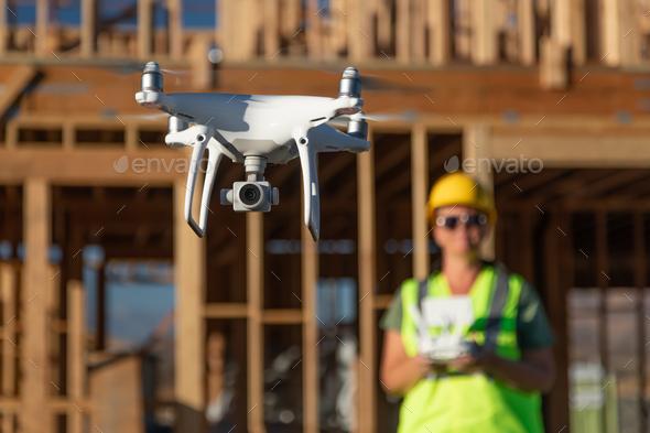 Female Pilot Flies Drone Quadcopter Inspecting Construction Site - Stock Photo - Images