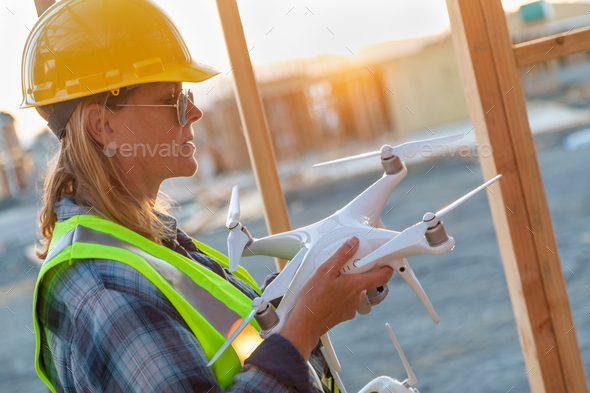 Female Unmanned Aircraft System (UAS) Quadcopter Drone Pilot Holding Drone at Construction Site - Stock Photo - Images
